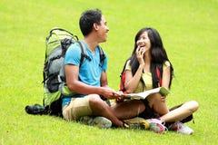 年轻亚洲夫妇聊天和坐草 库存照片