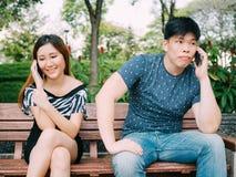 亚洲夫妇谈话在用不同的情感的电话- indi 库存图片