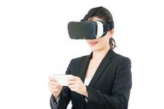 亚洲女商人用途巧妙的电话控制VR耳机 免版税库存照片