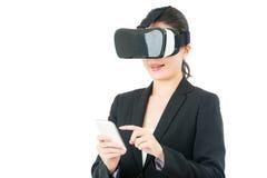 亚洲女商人用途巧妙的电话控制VR耳机 免版税库存图片