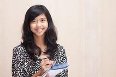 做她的任务高兴地的愉快的亚裔女实业家 免版税库存照片