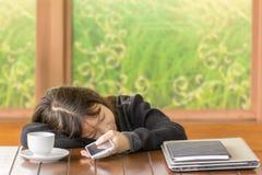 亚洲女孩在手中睡觉和举行智能手机 免版税库存照片