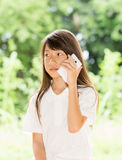 亚洲女孩用途巧妙的电话在庭院里 库存图片
