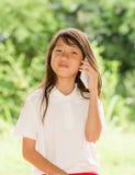 亚洲女孩用途巧妙的电话在庭院里 免版税库存图片