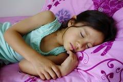 年轻亚洲女孩睡觉。 库存照片
