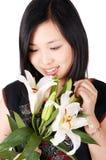 亚洲女孩藏品百合 免版税库存图片