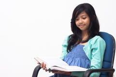 读亚裔的女孩坐椅子和她的书 免版税库存图片
