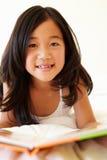 年轻亚洲女孩阅读书 免版税库存照片