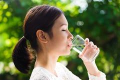 亚洲女孩饮料水 免版税库存图片