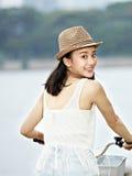 年轻亚洲女孩骑马自行车 库存照片