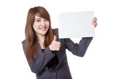 亚洲女实业家展示赞许拿着一个空白的标志 库存图片