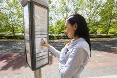 年轻亚洲女实业家读书信息标志侧视图在街道上的 库存图片