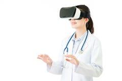 亚洲女性由VR耳机的医生检查耐心情况 免版税库存图片