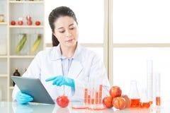 亚洲女性科学家接触研究的数字式片剂 免版税库存图片