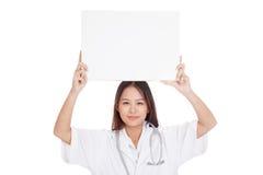年轻亚洲女性医生展示顶上一个空白的标志 免版税图库摄影