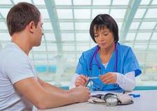 亚洲女性医生藏品和lookin医疗温度计 免版税图库摄影