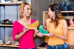 亚洲女朋友鞋子购物在商店 免版税图库摄影