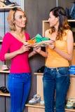 亚洲女朋友鞋子购物在商店 免版税库存图片