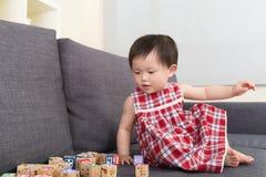 亚洲女婴戏剧玩具块和在家坐沙发 免版税图库摄影