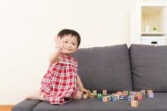 亚洲女婴戏剧玩具块和坐沙发 库存图片