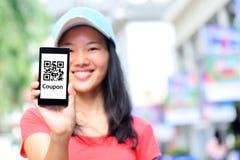 年轻亚洲妇女举行聪明的电话展示快的反应优惠券代码 免版税库存照片