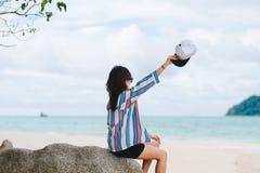 亚洲妇女坐岩石 手上升和拿着白色盖帽他 免版税库存图片