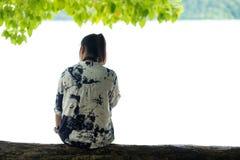 亚洲妇女坐木材在看风景视图的树下 Fr 库存照片