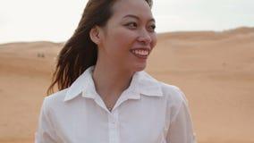 亚洲妇女微笑室外沙漠风吹的头发 股票视频