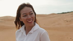 亚洲妇女微笑室外沙漠风吹的头发 影视素材