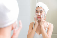 亚洲妇女清洁面孔皮肤开心与泡影cleansi 库存图片