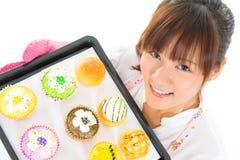 年轻亚洲妇女烘烤面包和杯形蛋糕 图库摄影