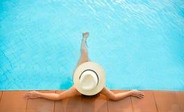 亚洲妇女生活方式松弛近的豪华游泳池sunbath,在海滩胜地的夏日 免版税库存图片