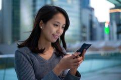 亚洲妇女看看手机 免版税库存照片