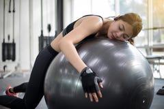 亚洲妇女睡着在做以后在健身房行使 适应 库存图片