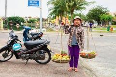 亚洲妇女蔬菜水果商运载的红毛丹芒果香蕉和manda 库存图片