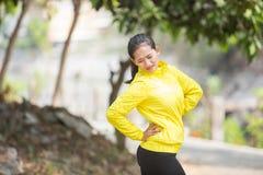 年轻亚洲妇女行使室外在充满痛苦的黄色霓虹夹克 库存照片