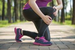 亚洲妇女赛跑者举行膝盖痛苦,人的腿 免版税图库摄影