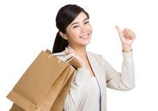 亚洲妇女赞许和举行与纸袋 免版税库存图片