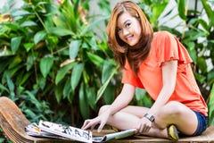 年轻亚洲妇女读书时装杂志 免版税库存照片