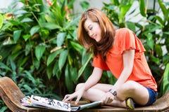 年轻亚洲妇女读书时装杂志 图库摄影