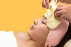 年轻亚洲妇女去除面部剥落面具 库存照片