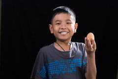 亚洲孩子在他的手上的拿着鸡蛋在黑背景 图库摄影
