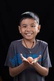 亚洲孩子在他的手上的拿着鸡蛋在黑背景 库存照片