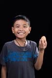 亚洲孩子在他的手上的拿着鸡蛋在黑背景 免版税库存照片