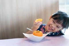 亚洲孩子女孩愉快吃新鲜的桔子 免版税库存图片