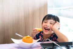 亚洲孩子女孩愉快吃新鲜的桔子 库存图片
