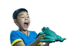 亚洲孩子拿着玩具青蛙的和神色非常惊吓 免版税库存照片