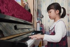亚洲孩子钢琴使用 库存照片