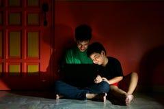 年轻亚洲孩子,兄弟或兄弟姐妹,有一台便携式计算机的在客厅 库存照片