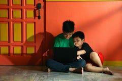 年轻亚洲孩子,兄弟或兄弟姐妹,有一台便携式计算机的在客厅 免版税库存照片